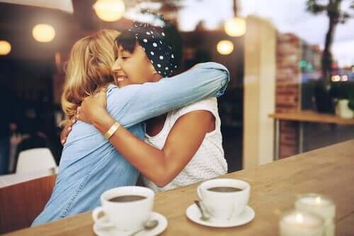 To veninder krammer, mens de får kaffe