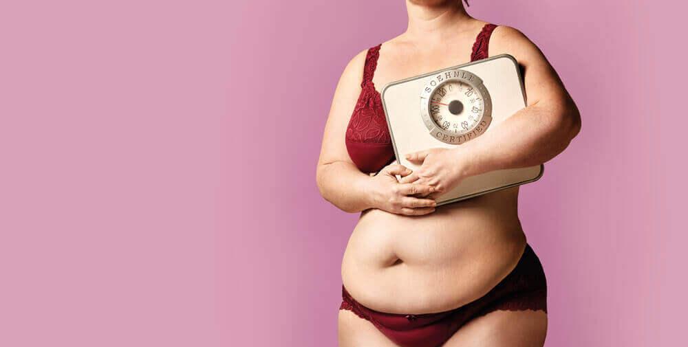 Overvægtig kvinde med vægt symboliserer sammenhængen mellem overvægt og skyld