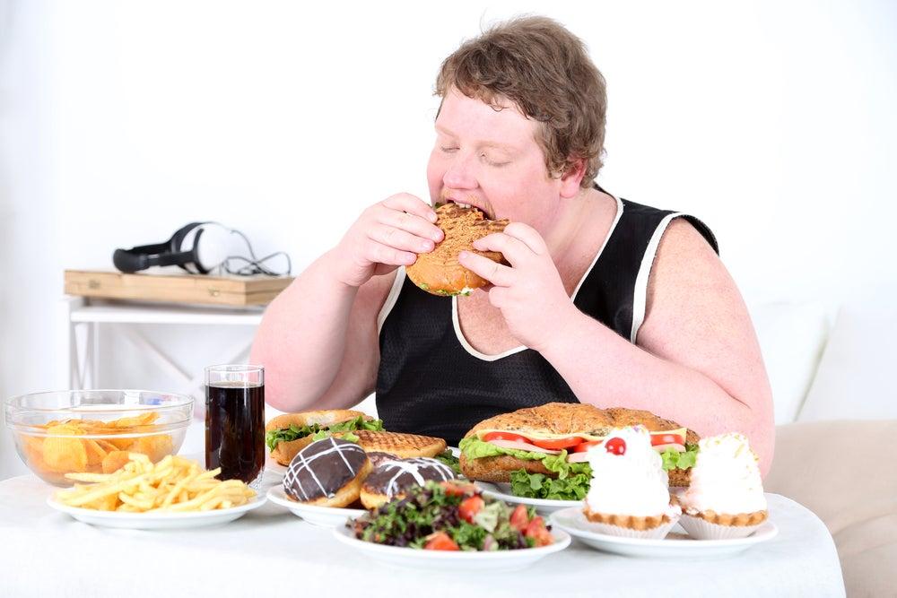 Person med alt for meget mad foran sig og burger i hånden