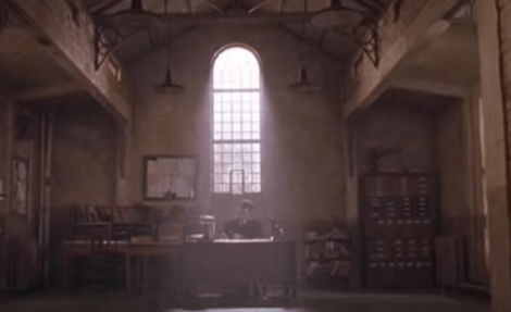 En mand, der sidder ved et skrivebord i et mørkt rum i et fængsel