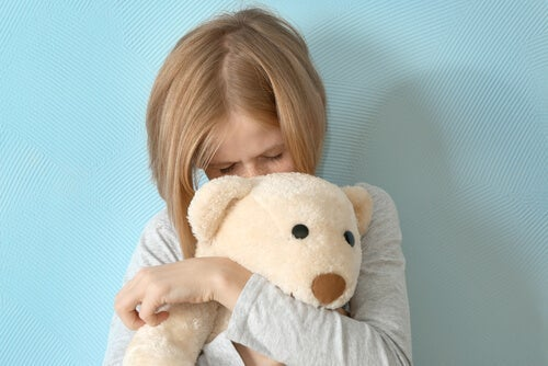 Pige, der krammer bamse, illustrerer humørforstyrrelser hos børn
