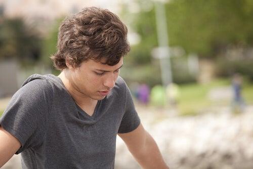 En teenager dreng kigger ned