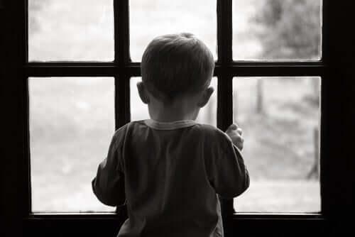 Lille dreng ser ud af vindue