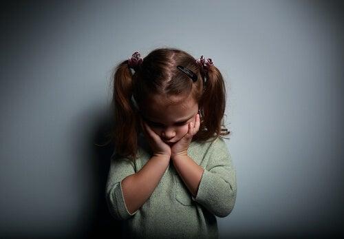 Trist pige tager sig til kinderne