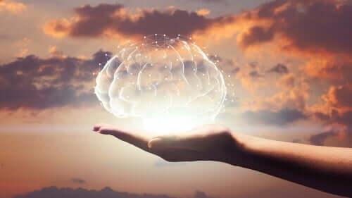 En hånd med et holografisk hjernebillede, der projicerer