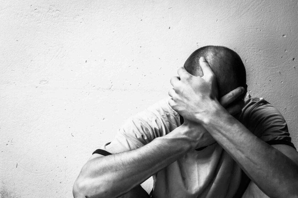 Mand skjuler ansigt bag hænder