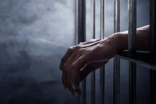 hænder, der stikker ud gennem tremmer, illustrerer formålet med kaution