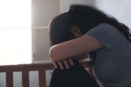 kvinde med armene over sine knæ oplever negativ selvopfattelse under en depression