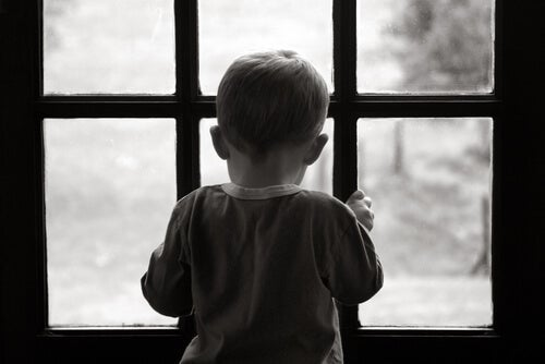 Dreng kigger ud af vindue og symboliserer depression hos børn