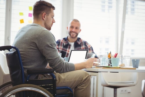 En mand i en kørestol sidder ved et bord og arbejder på sin bærbare computer og illustrerer inklusion af handicappede i samfundet