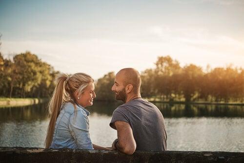 Mand og kvinde sidder ved sø