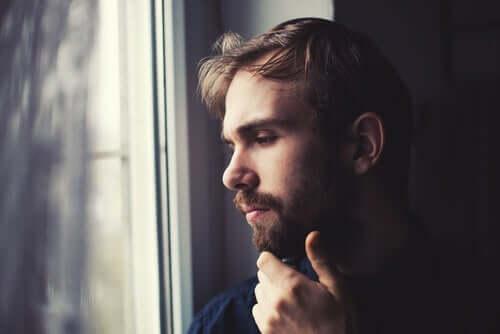 Mand ser ud af vindue og lider under en ubehandlet depression