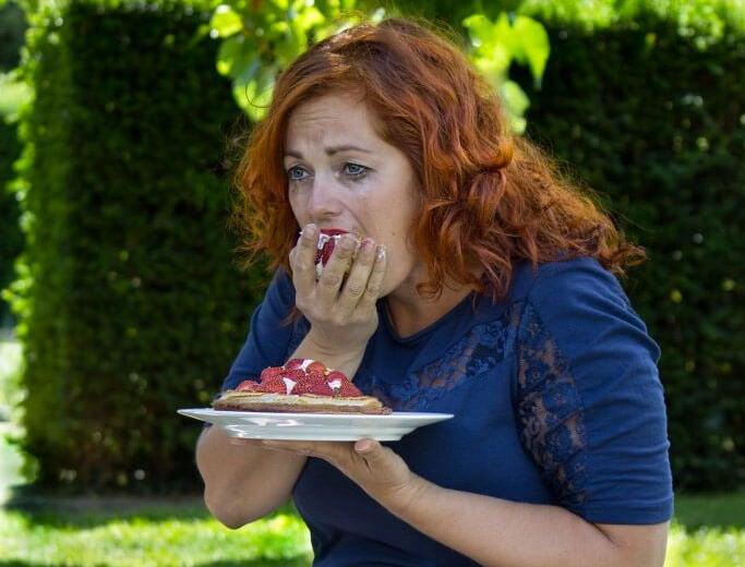 Grædende kvinde spiser en hel jordbærtærte