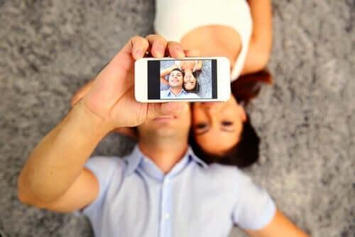 Par tager selfie sammen som en del af at foregive på sociale netværk