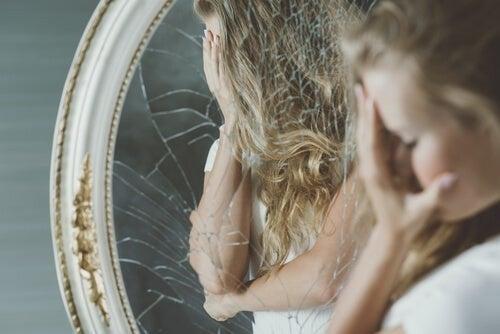 Nedtrykt pige står foran knust spejl