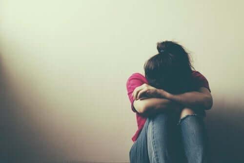 En pige græder med hovedet i armene som følge af risikabel adfærd hos teenagere