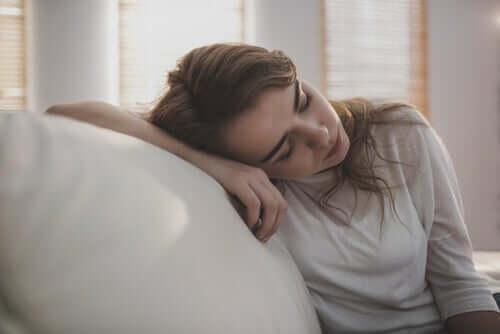 træt kvinde, der hænger på sofa