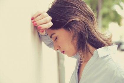 træt kvinde, der støtter sin pande mod væg