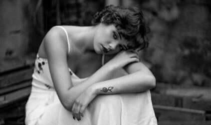 Trist kvinde hviler hoved på arm