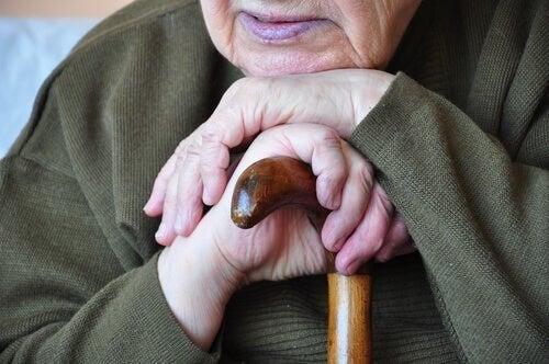 Ældre person hviler hovedet på sin stok