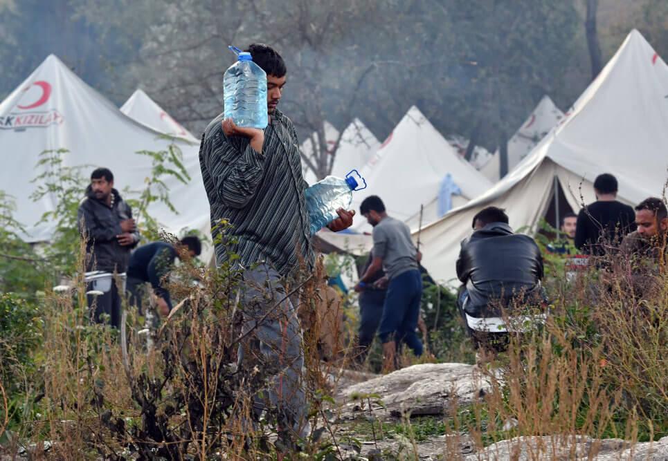 Mand i lejr går med vand som eksempel på støtte efter katastrofer