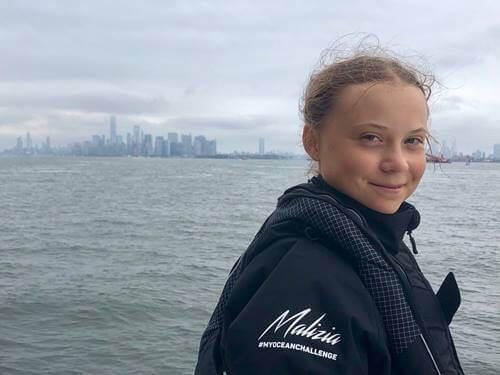Greta Thunberg smiler foran hav