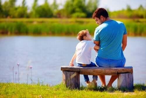 Far og søn ved sø viser, hvordan man kan sige undskyld til børn