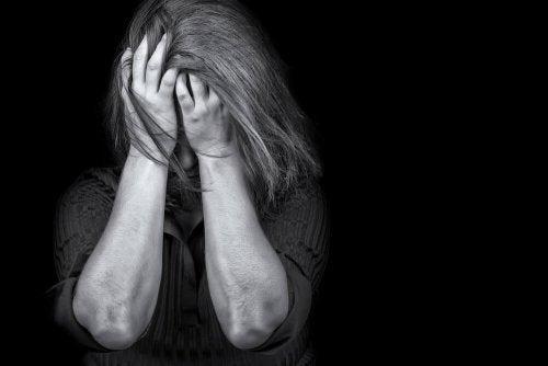 En kvinde med posttraumatisk stress tager sig til hoved