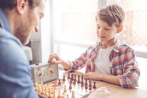 dreng spiller skak med voksen mand