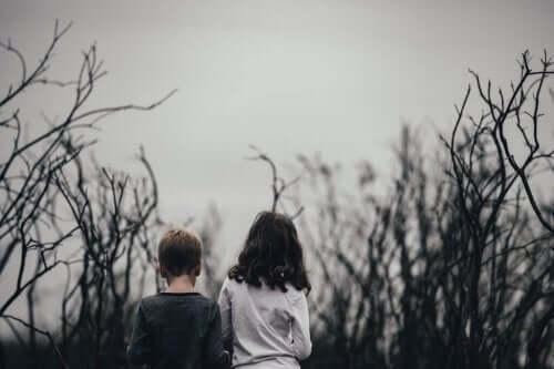 To børn ses bagfra i en vissen skov