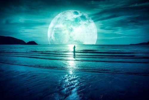dame i havet med kæmpe måne i baggrunden