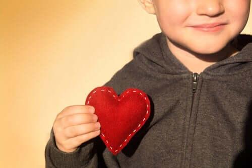 Dreng, der holder hjerte af filt, illustrerer, at man kan lære børn om taknemmelighed