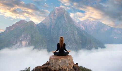 Kvinde på bjergtop udøver meditation som et middel mod mental træthed.