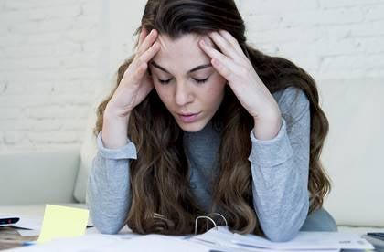 Kvinde ved skrivebord tager sig til hovedet og oplever mental træthed