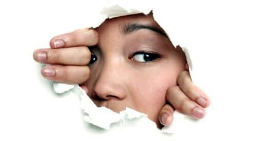 Kvinde bag lille hul i væg prøver at overvinde generthed