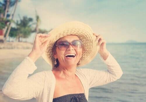 Smilende kvinde ved strand kan måle sin glæde med den subjektive glædesskala