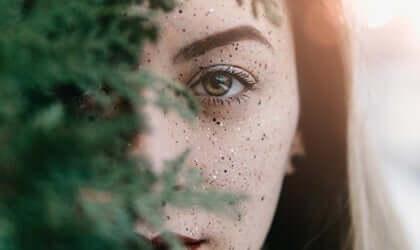 Kvinde ser ud bag træ