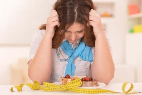 kvinde, der kigger opgivende på sin mad