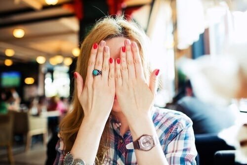 Kvinde skjuler sit ansigt med hænderne