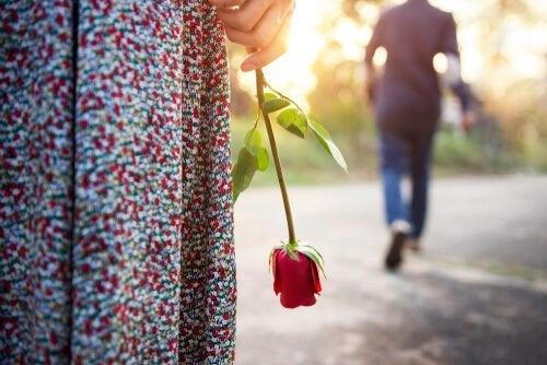 kvinde med rose hængende fra hånden