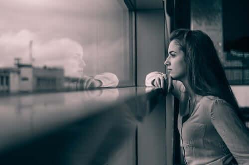 Kvinde ser eftertænksomt ud af vindue