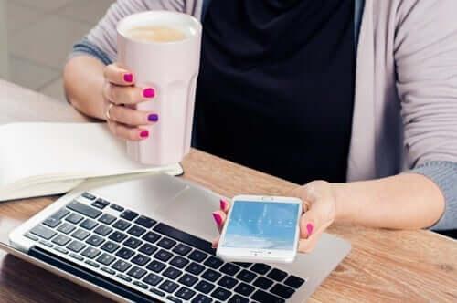 Kvinde med telefon og computer har svært ved at ignorere telefonen
