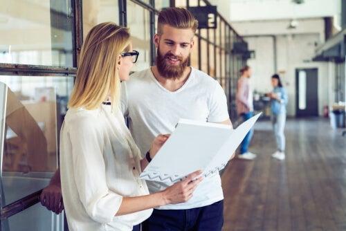 Kvinde viser mand mappe som eksempel på en god kollega