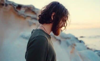 Mand alene ved strand tænker over, hvordan følelser er drivkraften i livet
