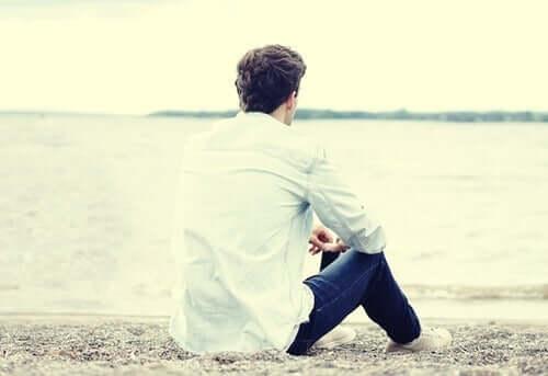 Mand alene på strand er i gang med at ignorere telefonen