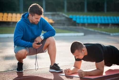 Mand, der træner anden mand i planken