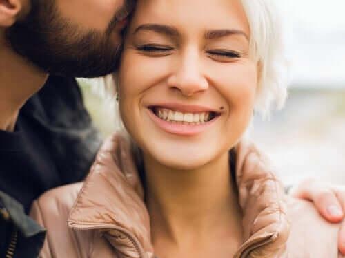 Mand kysser smilende kvinde i håret