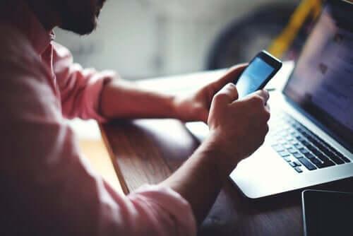 person, der bruger sin mobil foran sin computer