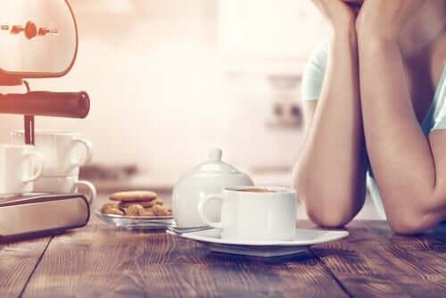 Søvnig person ved bord med kaffe