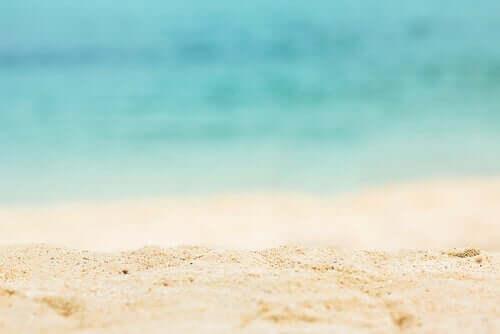 En strand med hvidt sand og blåt vand